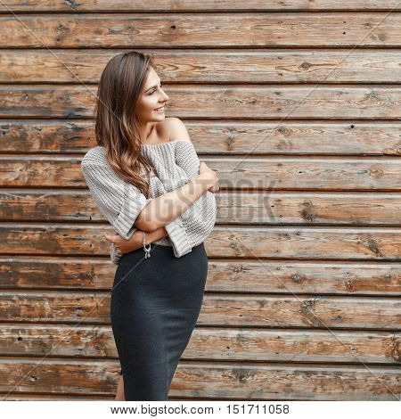 Fashionable Young Girl In A Gray Sweater And Black Skirt Near The Wooden Wall