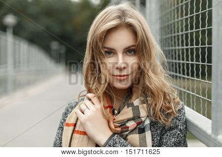 Portrait Of A Beautiful Young Blonde Woman In Autumn Vintage Scarf Near Metal Grate
