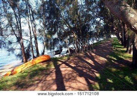 Anchored boats at waterside. Shady pathway at the river.