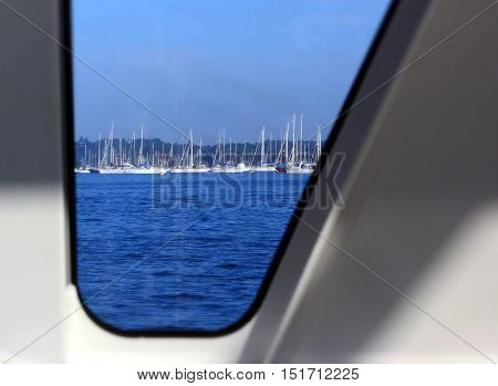 View of a harbour and yachts through porthole of cruise ship