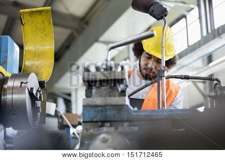 Low angle view of young manual worker working on machinery in metal industry