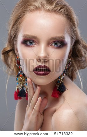 Beauty woman with beautiful make-up color . Blond hair raised hair jewelry on his neck clean skin beautiful face . Portrait shot in studio on a gray background .