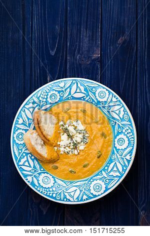 Creamy pumpkin soup in blue dish on navy background top view