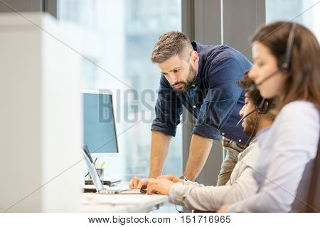 Mid adult businessman using laptop with coworkers wearing headsets in office