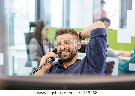 Smiling mid adult businessman talking on telephone in office