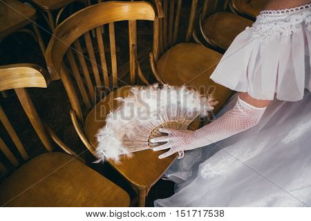 Girl in a lush white dress and in white gloves with beautiful hand fan