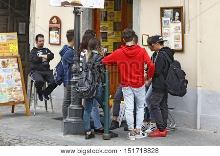 VENARIA REALE ITALY - OCTOBER 1: A Group of young tourist is going to freshen up in a fast food kiosk in the small town of Venaria Reale near Torino Italy on October 1 2016