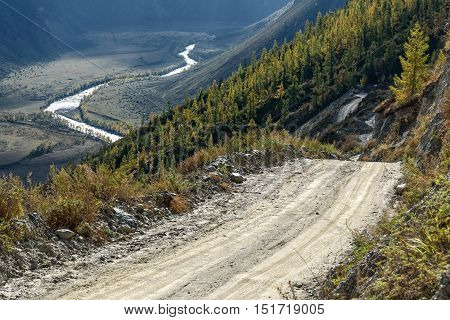 Scenic view of steep winding gravel mountain road through the pass part of the mountain serpentine passing the of the mountain the valley below and the river in the valley