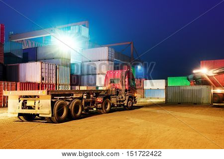 Container terminal at night stopped working forklifts and trucks.