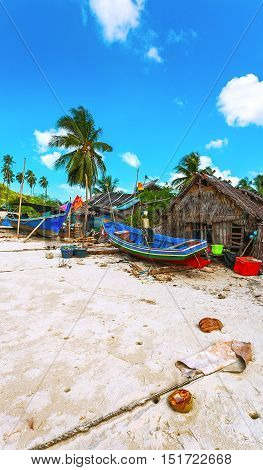 Fisherman's cottage on the sandy shore of the sea and colorful boats made of wood. Thailand