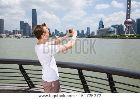 Side view of man photographing buildings while standing by railing in Shanghai