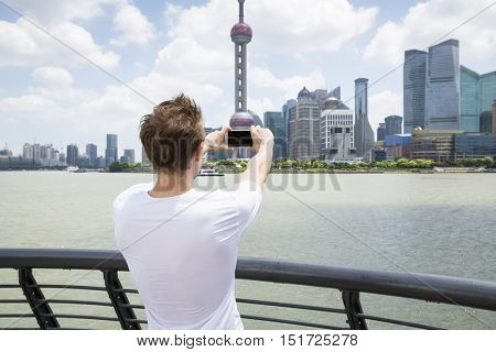 Rear view of man photographing Oriental Pearl Tower while standing by railing