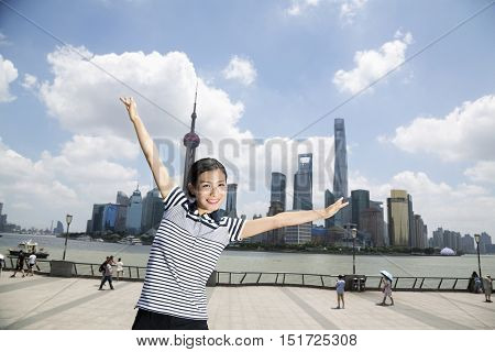 Portrait of happy woman standing with arms outstretched on promenade against Pudong skyline