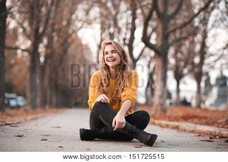 Smiling teenage girl 14-16 year old wearing casual autumn clothes sitting in park. Looking away. Happiness.
