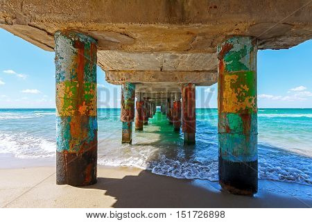 Under pier the ocean waves smashing to the pillars