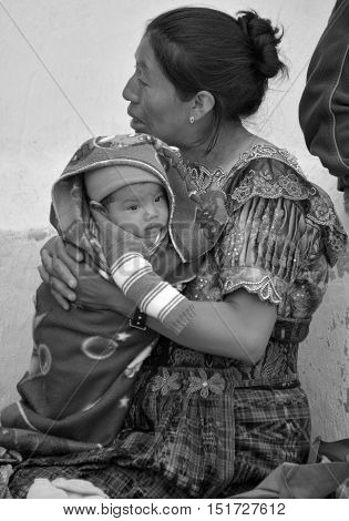 CHICHICASTENANGO GUSTEMALA APRIL 29 2016: Portrait of a Mayan baby hold by  his mother. The Mayan people still make up a majority of the population in Guatemala,
