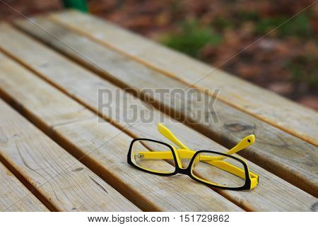Eyeglasses on a wooden bench, yellow and black plastic