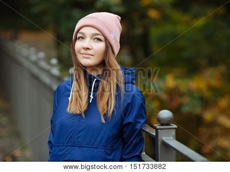 Stylish Sporty Brunette Woman In Trendy Urban Outwear Posing At Bridge Forest City Park On Cold Rain