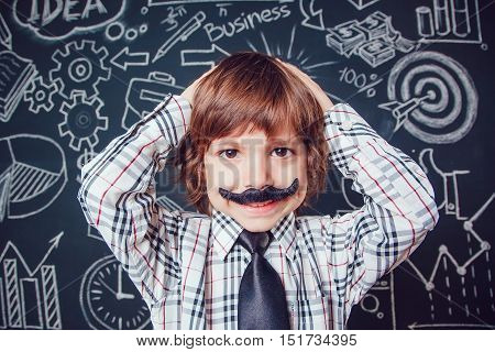 Little boy as businessman or teacher with mustache standing on dark background pattern. Wearing shirt and tie. He keeps holding his head