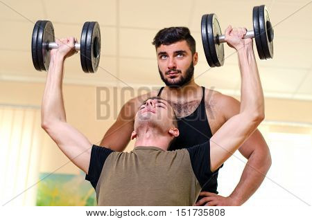 Man And His Personal Trainer Exercising With Dumbbells At The Gym. Technique Exercises For The Shoul