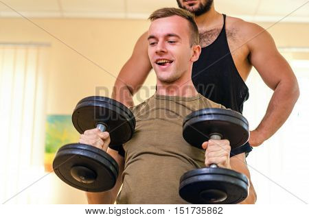 Man and his personal trainer exercising with dumbbells at the Gym. Technique exercises for the shoulders. novice athlete with coach