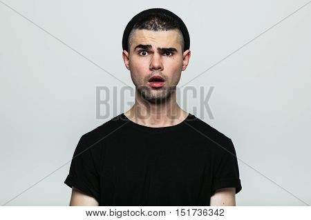 Portrait of young emotional shocked man in black hat with opened mouth. Studio shot on gray background.