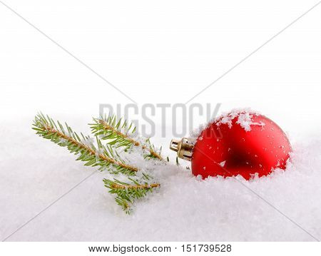 Red christmas ball on a green spruce twig  in snow.