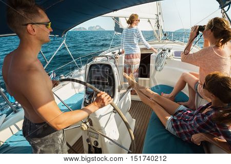 Young friends relaxing on the yacht in the blue sea