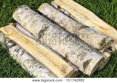 Chopped firewood of birch on a green background on the grass.