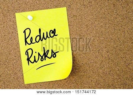 Reduce Risks Text Written On Yellow Paper Note