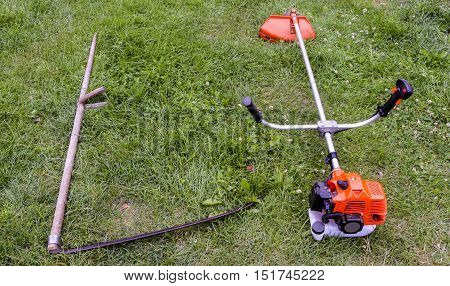 Spit and petrol trimmer for mowing grass, on a green background. The concept of changing technology.