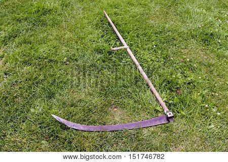 scythe for mowing grass, on a grass background.