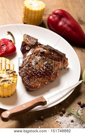 Grilled steak on brown wooden board with vegetables and spices, rustic background