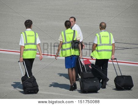 ORIO AL SERIO BERGAMO ITALY - CIRCA SEPTEMBER 2014: Ryan Air staff carrying their trolley on the runway towards the aircraft