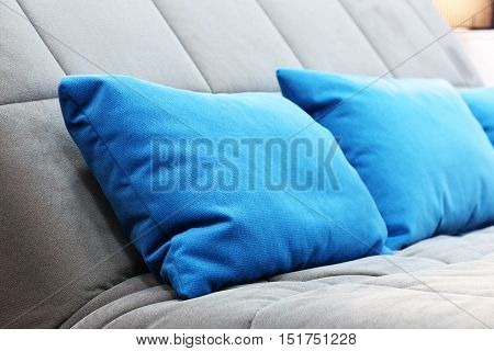 Blue pillows on a couch. Grey background
