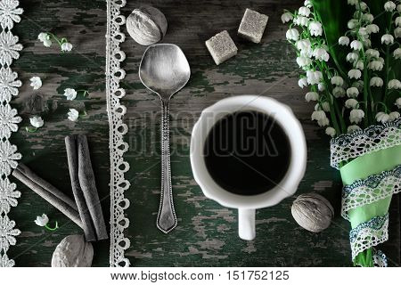 bouquet of lilies on wooden background and morning coffee