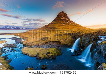 Kirkjufell Volcano Mountain with waterfalls in late winter, Iceland winter seson natural landscape