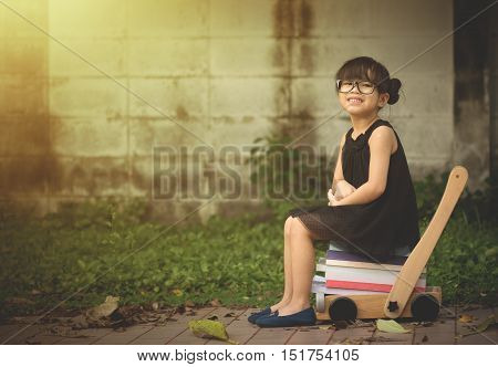 little girl sitting on stack of book