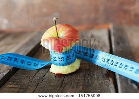 measurement on red bitten apple and wooden table