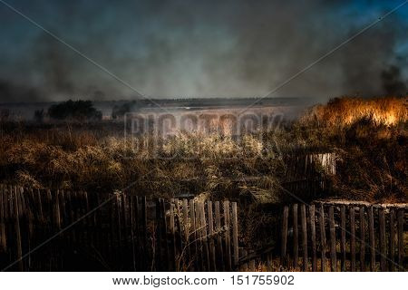 Ground fire - burning grass in the steppe. Dark, gloomy landscape. Clubs of smoke in the sky. Accident, man-caused disaster.