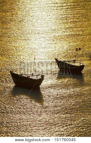 evening sea landscape with silhouettes of wooden boats. Sunset and reflection.