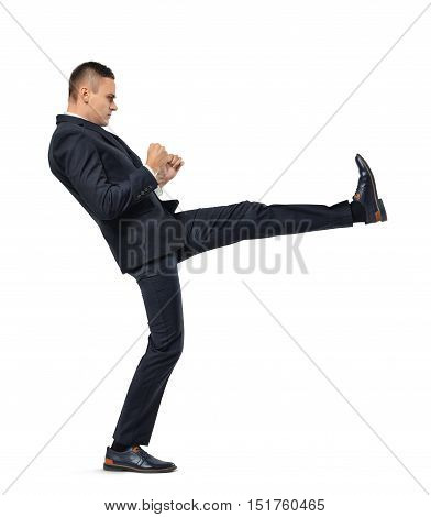 Young businessman kicking someone or something isolated on a white background. Struggling against something. Facing difficulties. Breaking barriers. Competitive spirit.