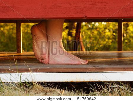 Close-up of a woman's bare feet scratching in a cabana at a beach with a warm evening light