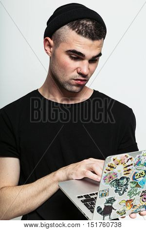 Saint-Petersburg, Russia - October 9, 2016. Studio shot of young brutal stylish man holding apple laptop plastered with stickers and looking at it grumpily while standing on grey background.