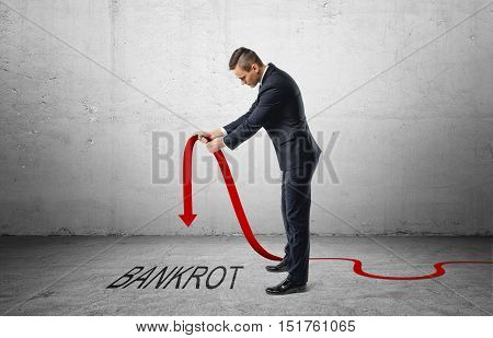Businessman holding a red line graph with a downturned arrow which is pointing to the word 'bankrot'. Falling incomes. Losing profit. Bankruptcy and insolvency.