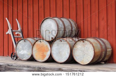 Vintage oil drums and a push cart against a red painted wooden wall.