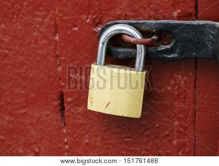Clos-up of a locked padlock on a red door.