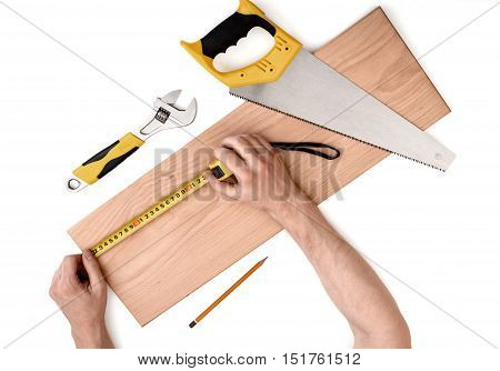 Close up view of a man's hands measuring wooden plank with tape line, isolated on white background. Tools and instruments.