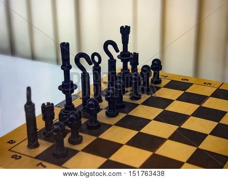painted black and white Screws,dowels, hooks, clamps, holders and fasteners and other small ironware on a chessboard used as chess pieces