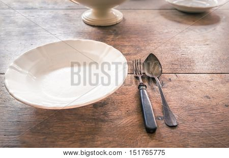Antique plate and tableware on aged wooden table - Rustic dinner settings with an old white dish and weathered metal fork and spoon placed on a wooden table with other crockery in the background.